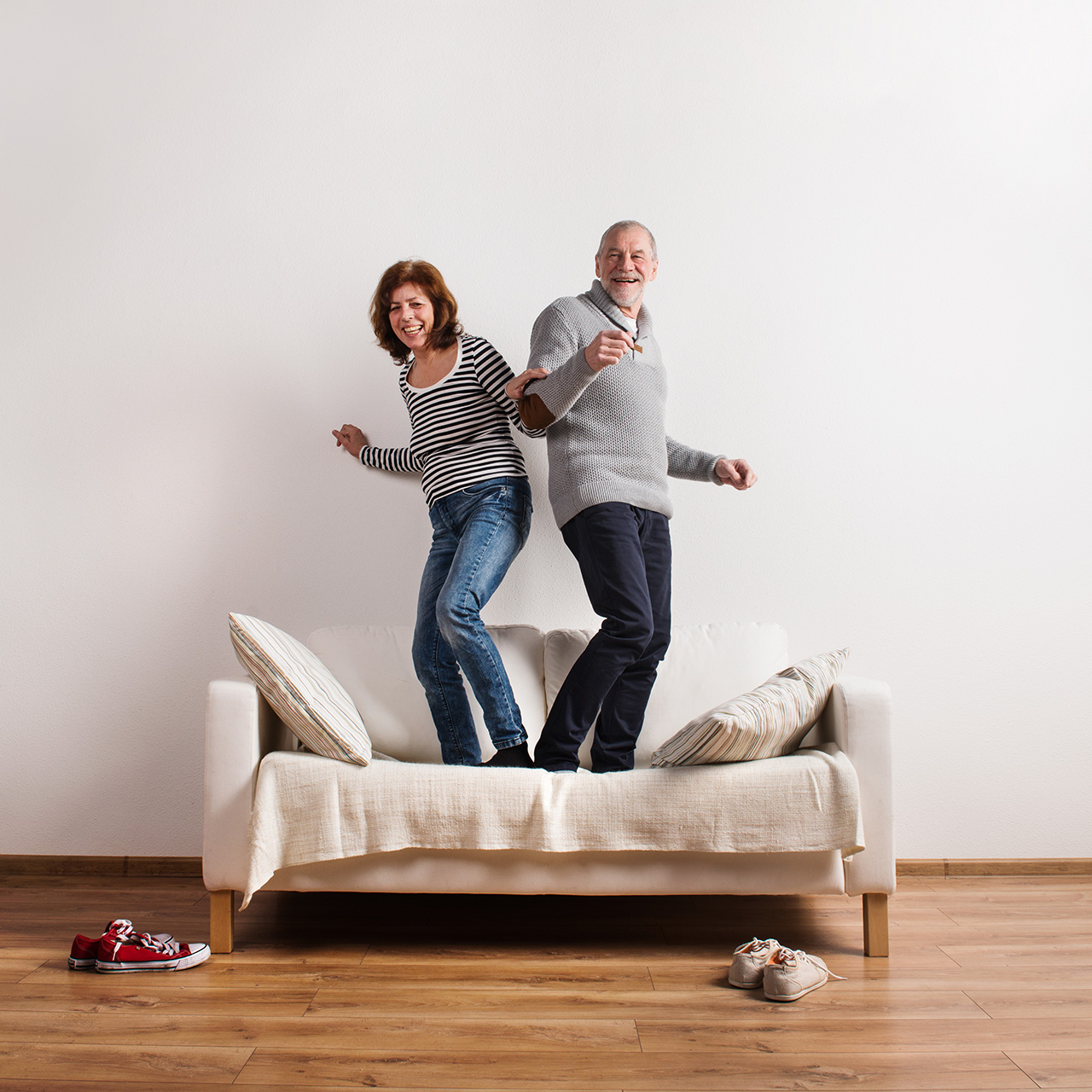 A pain-free couple dances on their couch.