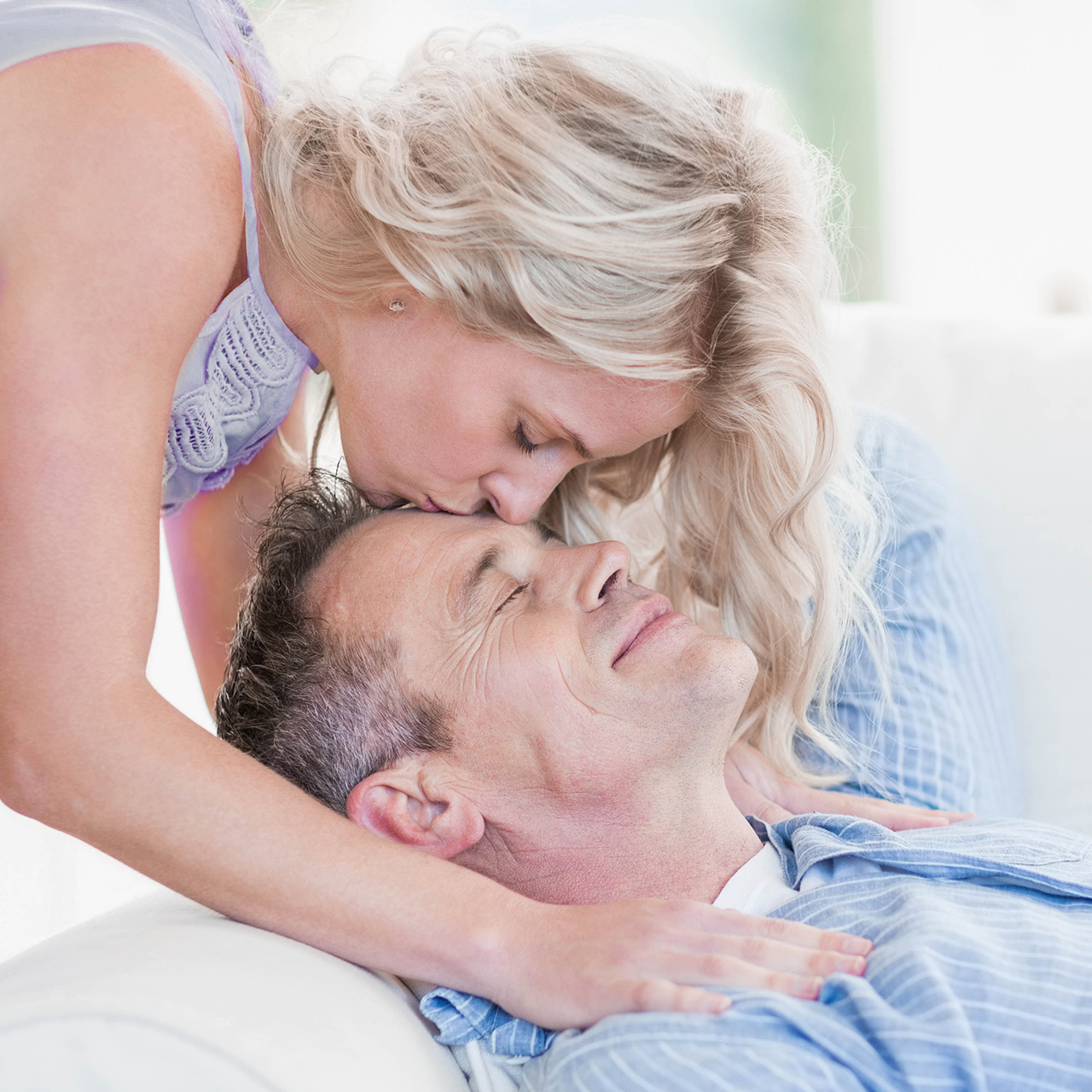 A woman gently kisses a smiling man on the forehead