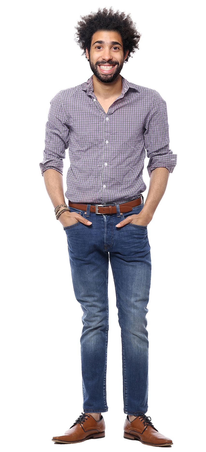 A man wearing a button-down, jeans, and oxfords stands confidently with his hands in his pockets.